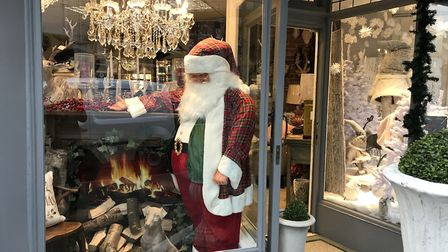 Santa warms up in the window of Just Trio.