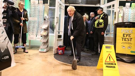 """Boris Johnson """"helps"""" with the clean up at an opticians as he visits Matlock, Derbyshire to view the"""