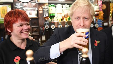 Boris Johnson, drinks from a pint at the Lych Gate Tavern in Wolverhampton. Photograph: Stefan Rouss