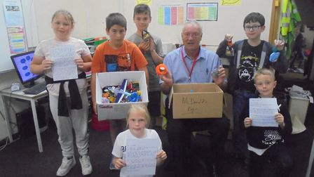 Bideford McDonald's franchisee David Hunt accepts Happy Meal toys from Year 5 pupils at West Croft P