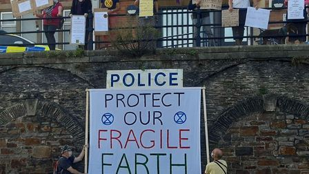 Extinction Rebellion members with banners displaying their 'crimes' at Bideford Police Station. Pict