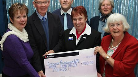 Newly wedded couple David and Shirley Holman are pictured presenting a cheque for £900 to Sidmouth's