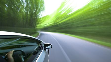 car driving fast into forest.