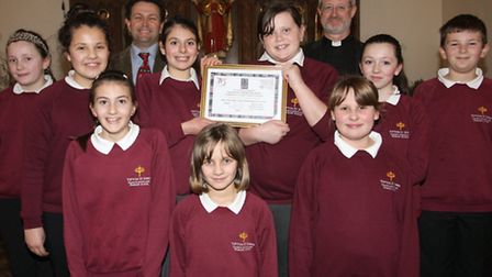 Pupils of Tipton St John CofE Primary School with their certificate presented by The Arch Deacon of