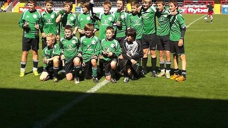 Sidmouth Town Under-14s with the Plate trophy at St James' Park after their win their in May.