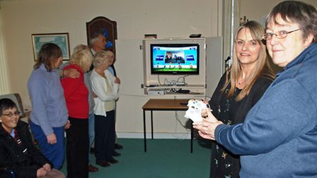 Yvonne White (front right) and Tina Cureton (front left) with an Xbox control as residents watch the