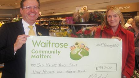 Sidmouth Waitrose branch manager Mark Shepherd presents a cheque for £990 to Annemarie Jones of the
