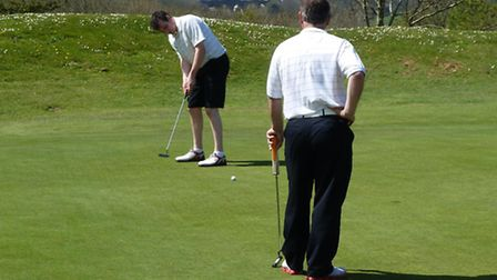 Damein Gee putts out watched by Neil Holland at Sidmouth