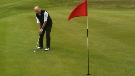 Colin Mitchell practises putting prior to his match in the meeting with Minehead