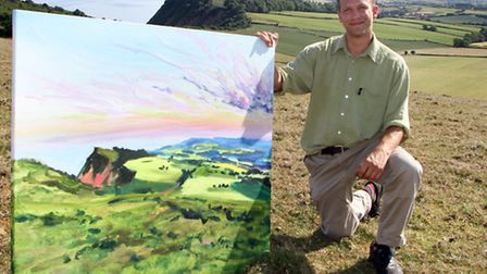 Sidmouth artist Joe Webster who teaches art at Sidmouth College with one of his paintings at Peak Hi