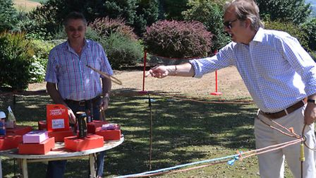 MP Hugo Swire tries his hand at the hoopla stand after opening a new sensory garden at Angela Court
