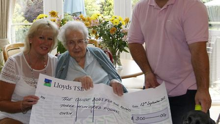 Holmsley nursing home resident 103 year old Margaret Mills hands over a cheque to Adrian Sparkes of