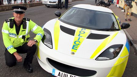Sgt. Andy Squires admires a Lotus police car ahead of the Tour of Britain start in Sidmouth. Picture