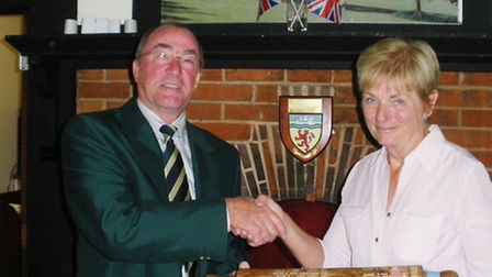 John Rockey accepts the rolling pin trophy from ladies' captain Ros Eaton
