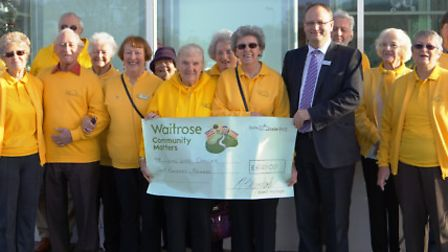 Members of Sidmouth Living With Cancer gratefully recive a cheque from Waitrose.