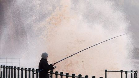 A lone fisherman during rough seas at Sidmouth. Picture by Alex Walton. Ref shs 2118-01-14AW. To ord