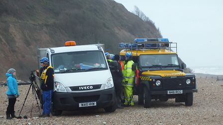 Coatguards standby on Seaton beach as millions of cigarettes are removed from a washed up shipping