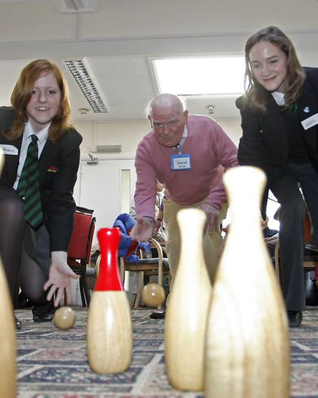 Michaela and Demi from Sidmouth college dementia friends playing skittles with David Beale at the Si