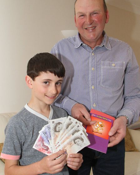 Mike Brown from Sidford presents Jacob Taylor, eleven, with a thank you gift for returning some cash