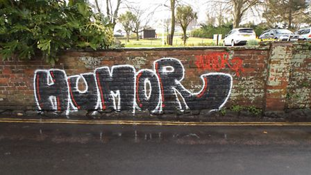 Graffiti that defaced an ancient wall at Kennaway House was scrubbed off by two members of the publi