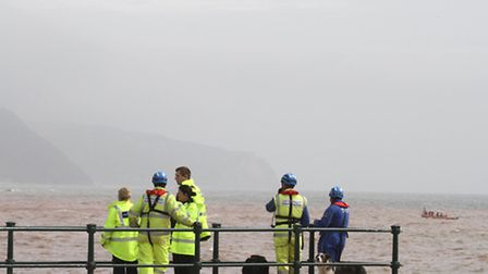 The Sidmouth lifeboat and the Portland helicopter are pictured on scene with Police and a team from
