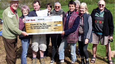 Handel Bennett hands to Kati Fitzhenry and Friends of the Byes a £640 cheque for wild flower seeds –