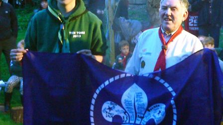 Brian Foulkes is presented with a world Scout flag signed by all past and present members of the cub