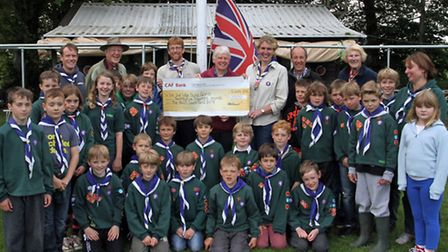 Peter Moss of the Sid Owen Fund handing over a cheque to John and Kirsty Hammond of Sidmouth Scouts.