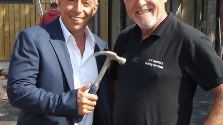 Sidmouth Garden Centre owner Ian Barlow with carpenter Nigel Membury and his new hammer