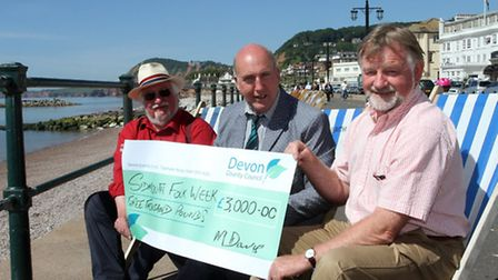 Stuart Hughes handing over a locality fund grant to John Braithwaite for Sidmouth folk week. Photo b