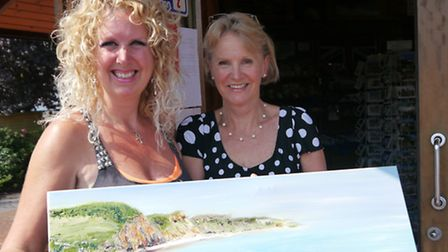 Artist Jacqueline Steel with one of her paintings of Sidmouth. She is pictured with Mandy Newman, of