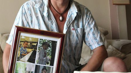 Sidford resident Ralph Leadbetter with photographs of his family who remain in Indonesia unable to l