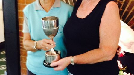 Sidmouth golfer Penny Ashby receiving the trophy for winning the County Venerable Vets Competition a