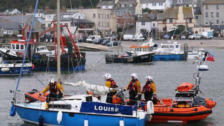 The yacht Louise being towed into Lyme Regis Harbour by the RNLI lifeboat. Photo by Richard Horobin