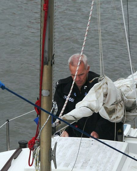 A police officer aboard the yacht Louise. Photo by Richard Horobin