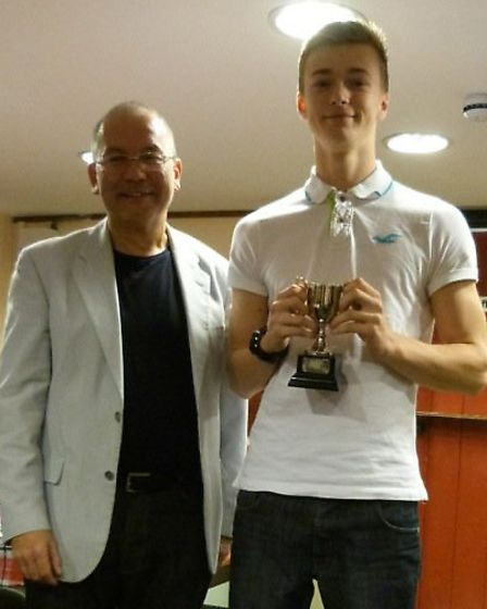 Jake Harrison receives the Sidmouth Tennis Clubmen's single's trophy from club chairman Peter Fung