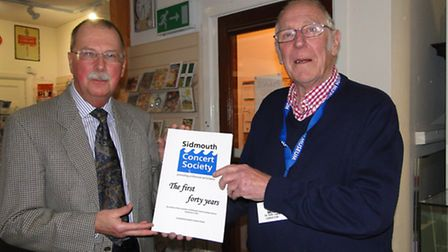 Sidmouth Concert Society chairman Stephen Huyshe-Shires presenting the book to Sidmouth Museum curat