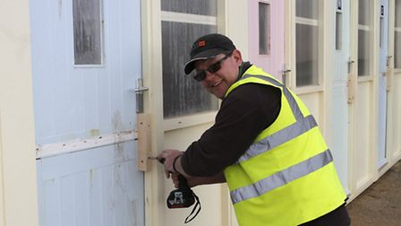 Barry Bending, maintenance technician with street scene,making good the Sidmouth beach huts after th