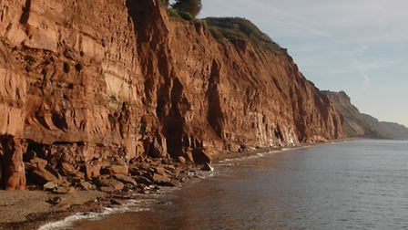 The Jurassic Coast at Sidmouth showing the red rocks of Salcombe Cliffs