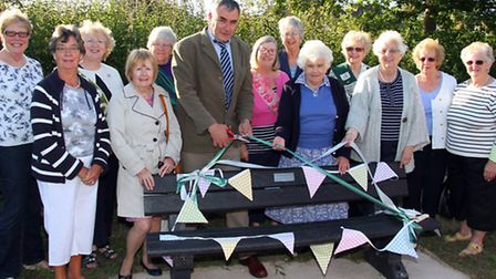 Dr Todd Gray cuts the ribbon to the new Sidford WI bench, which was installed in the Byes to mark th