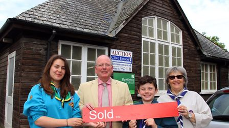 The 1st Sidmouth Scouts are celebrating after having sold their hut at auction. At the hut are beave