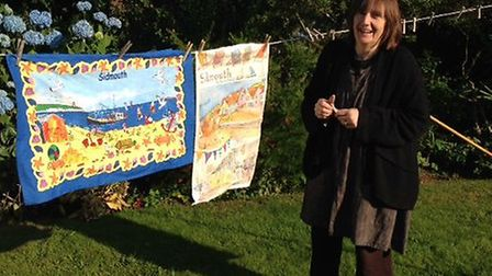 Barabara Howard with the two tea towels that she bought from Sidmouth.