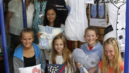 Sidmouth college textile students in the window at the Devon air ambulance shop with Debbie Collingw