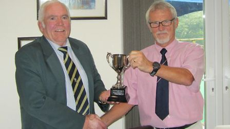 Sidmouth B captain Colin Macklin (left) is presented with the Jurassic Cup after his team retained t