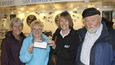 Mary and Stan Bagwell along with Christine Hardy present a cheque to Gina Moore of the fishermens mi