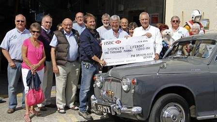 Ian Hartnell of the P4 Drivers Guild Devon hands over a cheque to John Fowler and Phil Shepperd of t