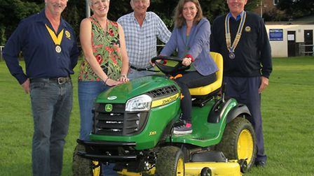 Claire Wright is pictured in the driving seat of the new lawnmower at Ottery St Mary football club w