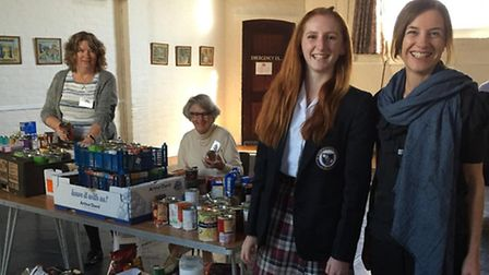 Volunteers from the Sid Valley Food Bank and students from St John's International School sort throu