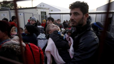 Migrants and refugees wait to board a train heading towards Serbia at the transit center for refugee