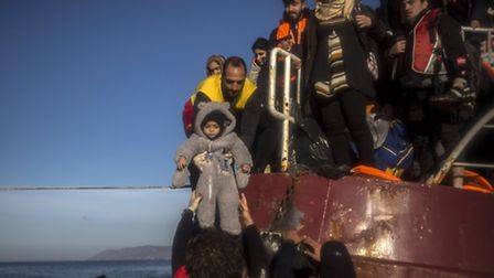Volunteers help around 150 refugees and migrants, mostly from Syria and Iraq, to disembark from a ve